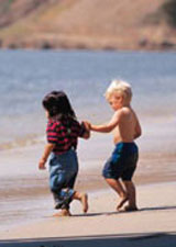Little girl and boy running on the beach holiding hands